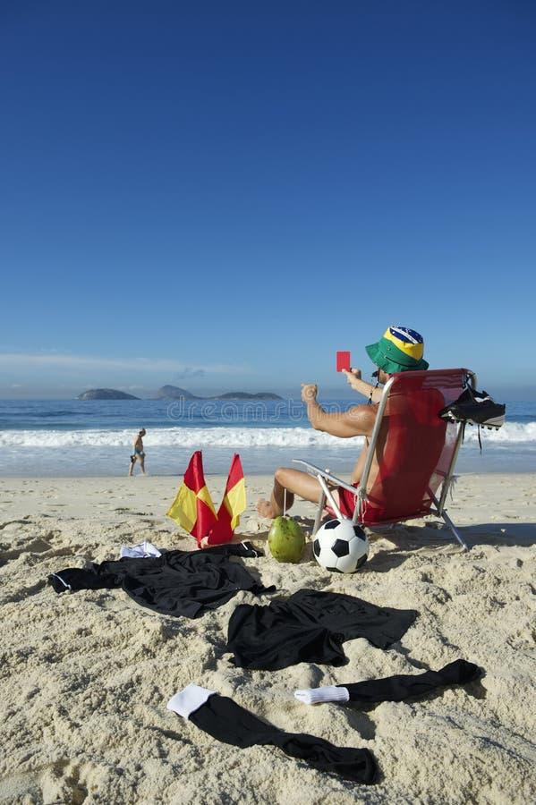 Árbitro Relaxing del fútbol del fútbol en la silla de playa el Brasil imagen de archivo libre de regalías