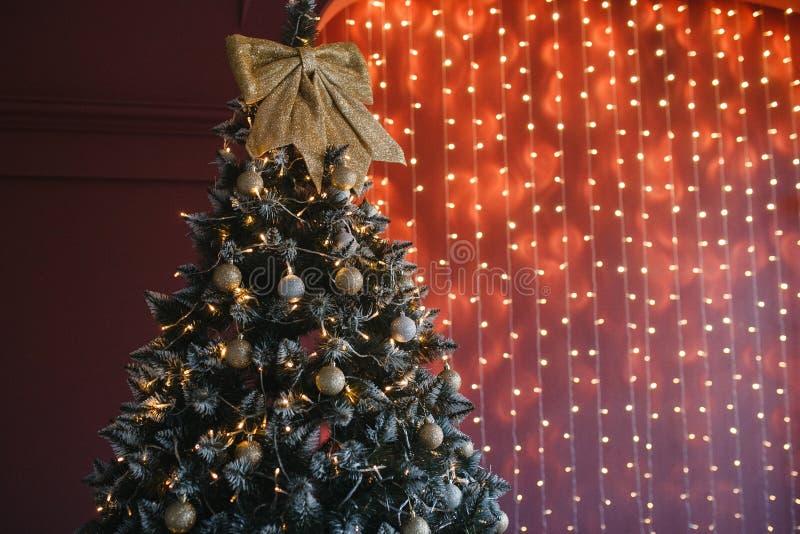 Árbol adornado de la Navidad y del Año Nuevo con la decoración del oro en fondo del bokeh de las luces de la guirnalda en la pare fotografía de archivo