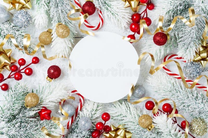 Árbol de abeto Nevado, espacio en blanco de papel redondo y decoraciones de la Navidad en la opinión de sobremesa de madera blanc fotografía de archivo