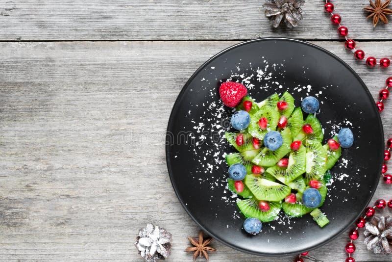 Árbol de Kiwi Christmas idea divertida de la comida para los niños Fondo de la comida de la Navidad y del Año Nuevo foto de archivo