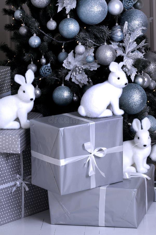 Árbol de navidad Año Nuevo Regalos bajo el árbol figuras del conejito imagen de archivo