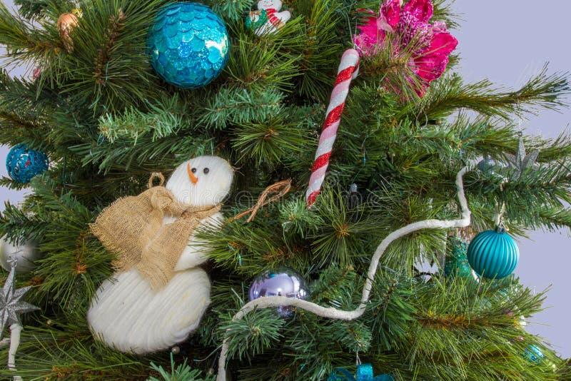 Árbol de navidad adornado con decoros prominentes del muñeco de nieve y del palillo foto de archivo