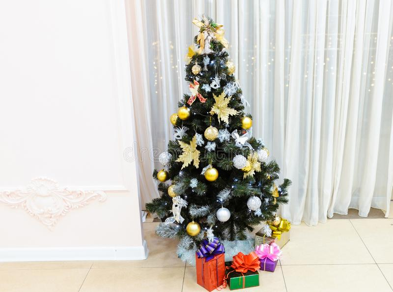 Árbol de navidad adornado con los juguetes con los regalos en cajas debajo de él en un fondo ligero imágenes de archivo libres de regalías