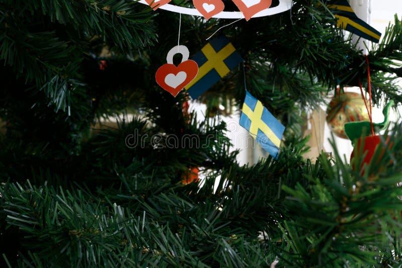 Árbol de navidad adornado con varias banderas de papel suecas imagenes de archivo
