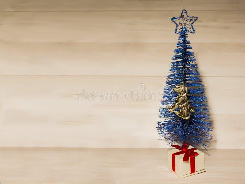 Árbol de navidad azul artificial de la Navidad pequeño en un fondo marrón fotos de archivo