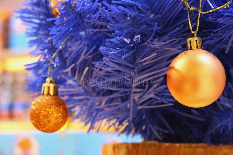 Árbol de navidad azul con los bulbos amarillos Rama de árbol artificial azul de pino con las bolas de oro Decoración festiva de l foto de archivo
