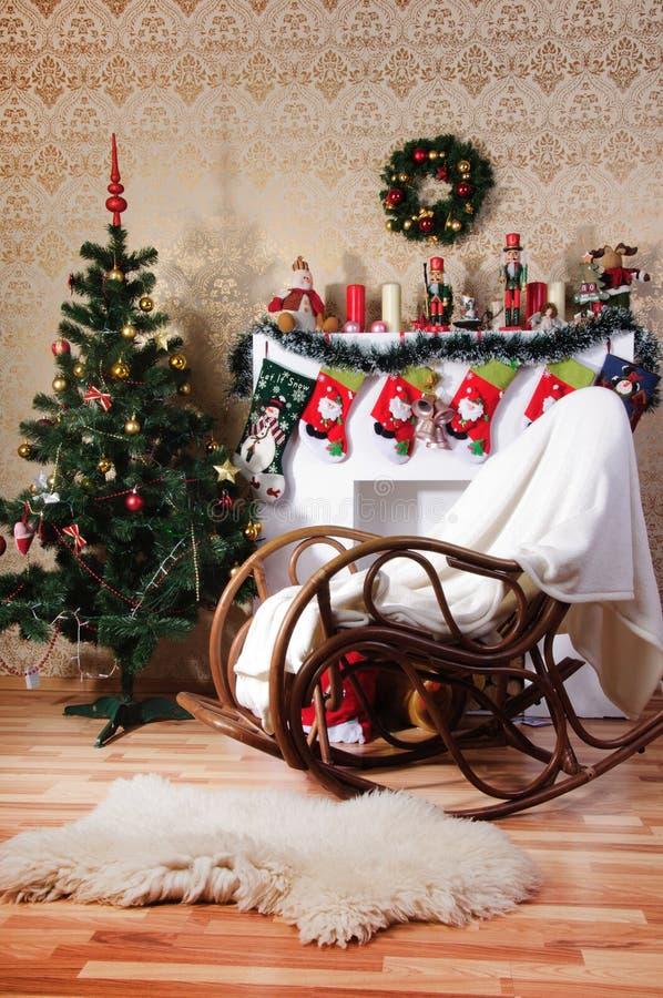 Árbol de navidad, chimenea adornada y mecedora en interior fotografía de archivo
