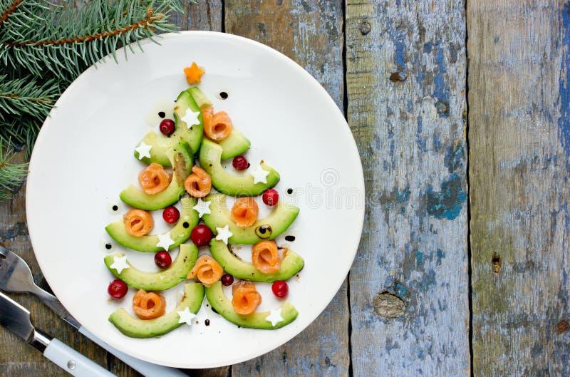 Árbol de navidad comestible delicioso de rebanadas de aguacate, de salmones salados, del arándano y de las estrellas hervidas del foto de archivo