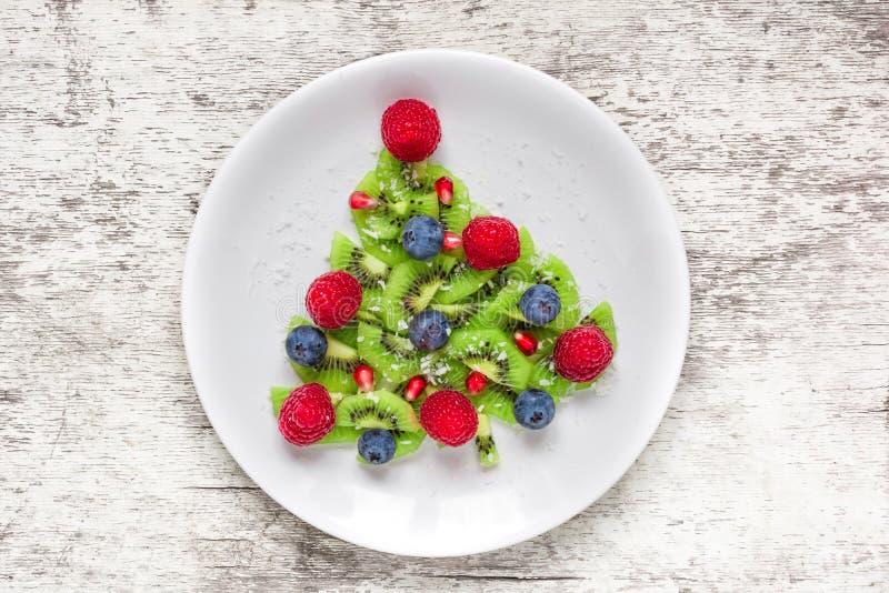 Árbol de navidad comestible divertido hecho de las frutas y de las bayas Idea del desayuno de la Navidad para los niños fotos de archivo