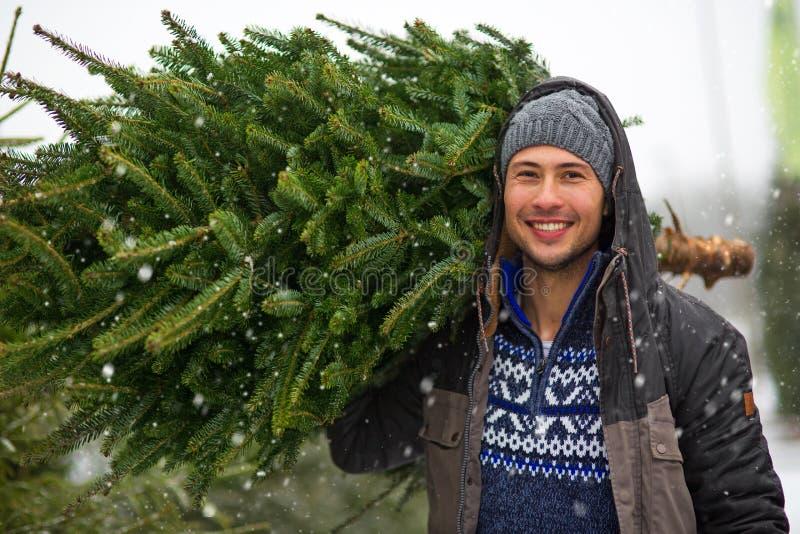 Árbol de navidad de compra del hombre joven imagenes de archivo