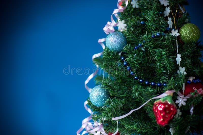 Árbol de navidad con las decoraciones en un fondo azul imagen de archivo libre de regalías