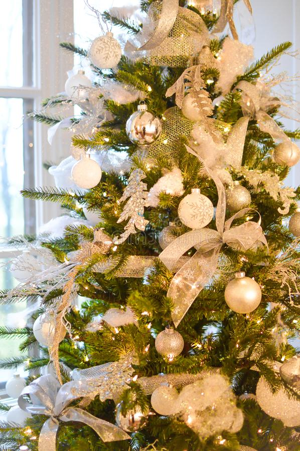 Árbol de navidad con las decoraciones de plata y blancas foto de archivo