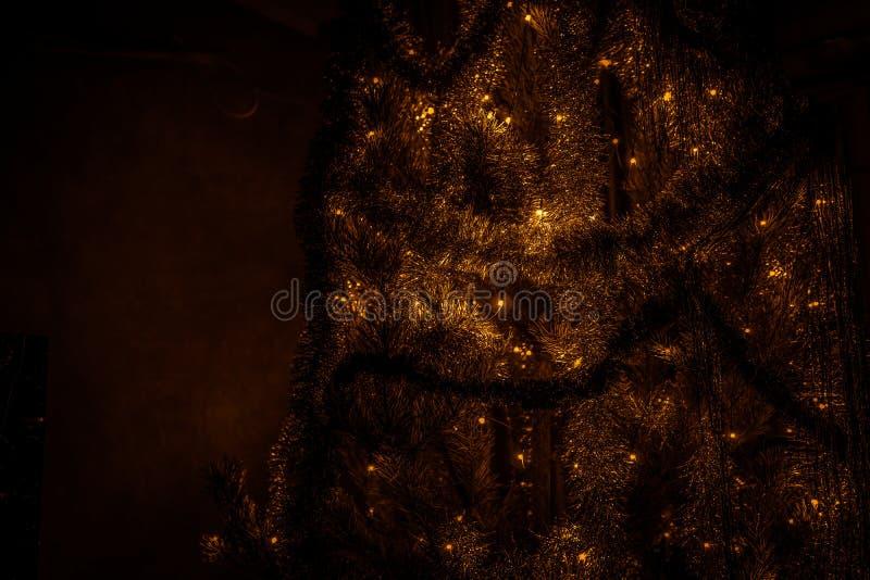 Árbol de navidad con las decoraciones y el primer de la guirnalda imagenes de archivo