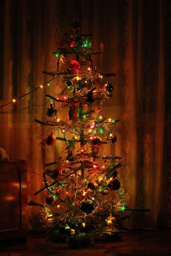 Árbol de navidad con las decoraciones y las guirnaldas en el hogar fotografía de archivo