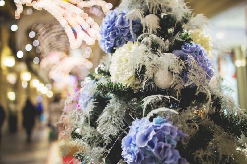 Árbol de navidad con las flores blanco-púrpuras imagenes de archivo