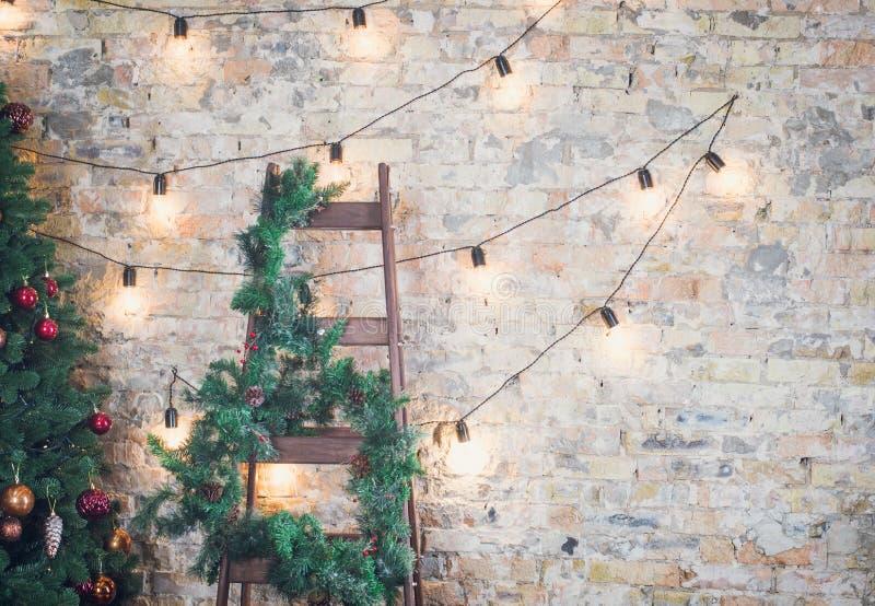 Árbol de navidad con las guirnaldas en un fondo de la pared de ladrillo fotos de archivo