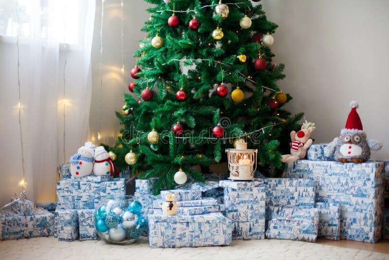 Árbol de navidad con las porciones de presentes debajo del árbol, luces y imagenes de archivo
