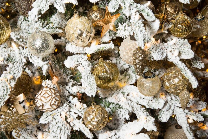 Árbol de navidad con las ramas blancas y las decoraciones de oro de la Navidad foto de archivo