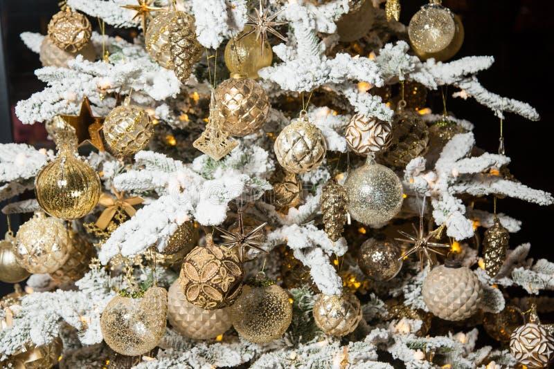 Árbol de navidad con las ramas blancas y las decoraciones de oro de la Navidad fotografía de archivo libre de regalías