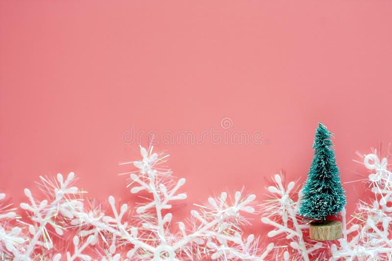 Árbol de Navidad con los ornamentos del copo de nieve y decoración en backgr rosado imagen de archivo