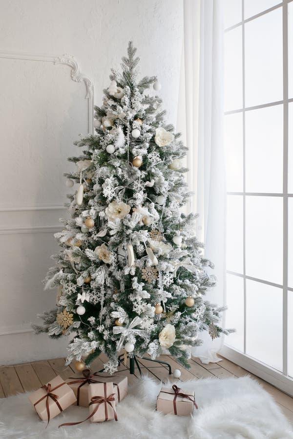Árbol de navidad con los presentes debajo en sala de estar imagen de archivo