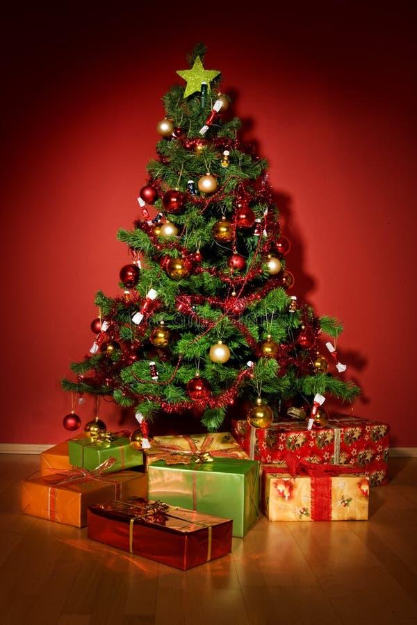 Árbol de navidad con los regalos de la Navidad en sitio rojo foto de archivo libre de regalías