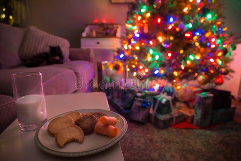 Árbol de navidad con los regalos debajo de él y galletas y leche dejados hacia fuera para Papá Noel y el reno imágenes de archivo libres de regalías