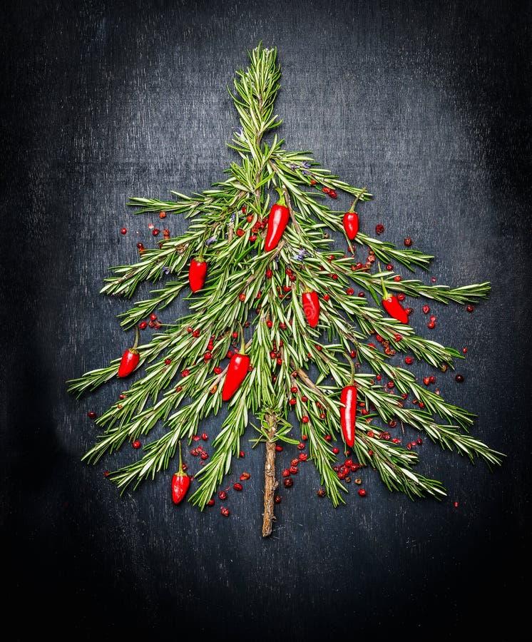 Árbol de navidad de la comida hecho del romero fresco y del chile rojo en fondo oscuro fotos de archivo libres de regalías