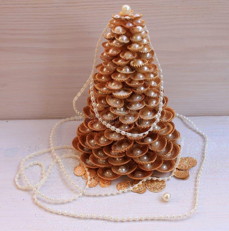 Árbol de navidad de oro hecho a mano de conchas marinas en un fondo blanco fotografía de archivo
