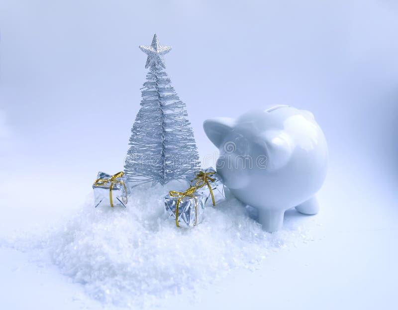 Árbol de navidad decorativo, caja de dinero de cerámica del cerdo y cajas de regalo en fondo mullido de la nieve fotografía de archivo libre de regalías
