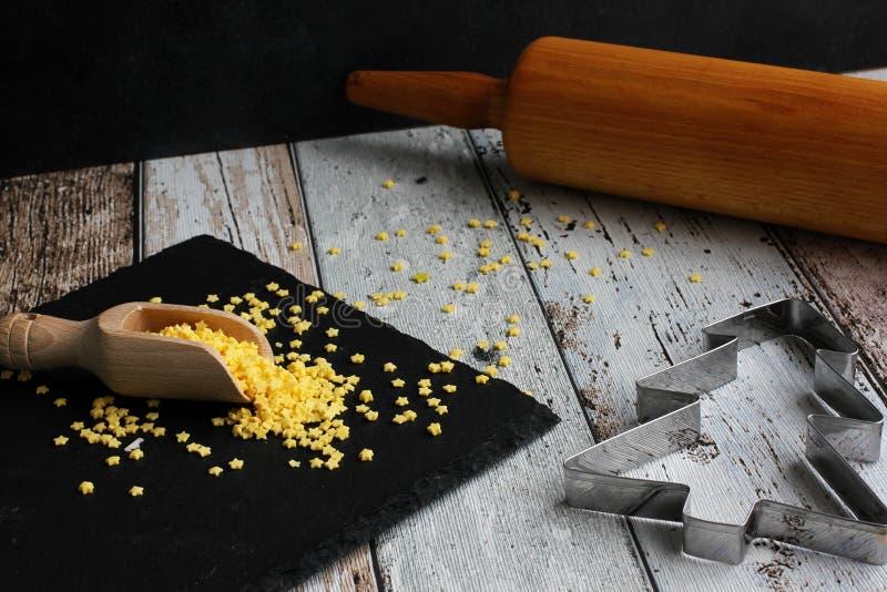Árbol de navidad del cortador de la galleta de la Navidad y estrellas amarillas del azúcar con el rodillo en la tabla de madera imagenes de archivo