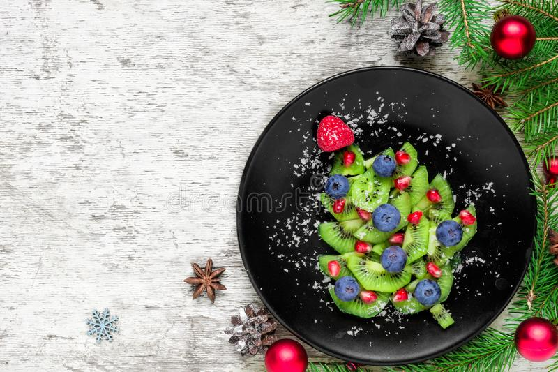 Árbol de navidad del kiwi con las bayas y el coco con las ramas de árbol de abeto y decoraciones sobre la tabla de madera blanca fotografía de archivo libre de regalías