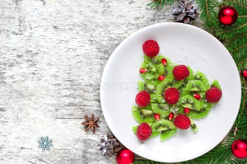 Árbol de navidad del kiwi con las frambuesas, la granada y el coco con los conos del pino idea divertida de la comida para los ni imagen de archivo libre de regalías