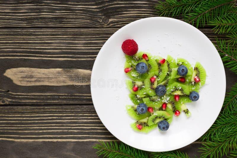 Árbol de navidad del kiwi con las ramas de árbol de abeto sobre la tabla de madera rústica idea divertida de la comida para los n foto de archivo