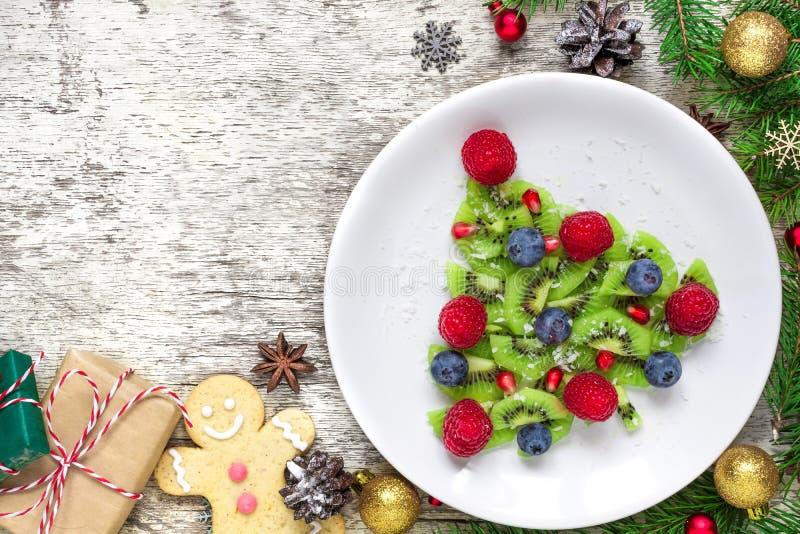 Árbol de navidad del kiwi con las ramas de árbol de abeto y las cajas de regalo sobre la tabla de madera blanca idea divertida de fotos de archivo libres de regalías