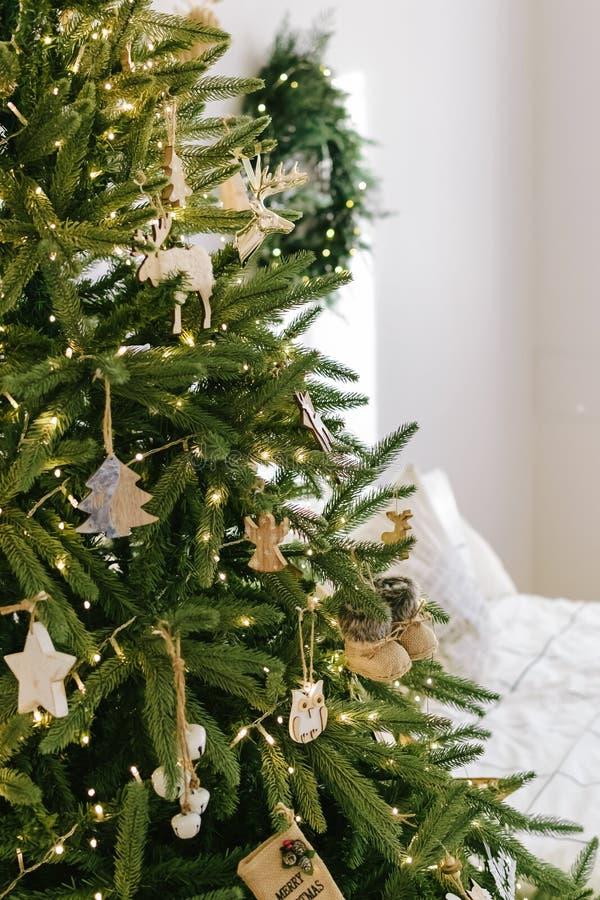 Árbol de navidad en el dormitorio adornado con los juguetes de madera del árbol de navidad del estilo rústico del vintage imagen de archivo libre de regalías