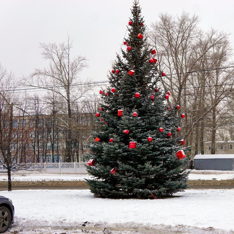 Árbol de navidad en la calle adornada con las bolas y los giftboxes rojos fotografía de archivo libre de regalías