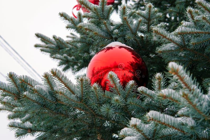 Árbol de navidad en la calle adornada con las bolas y los giftboxes rojos imagenes de archivo
