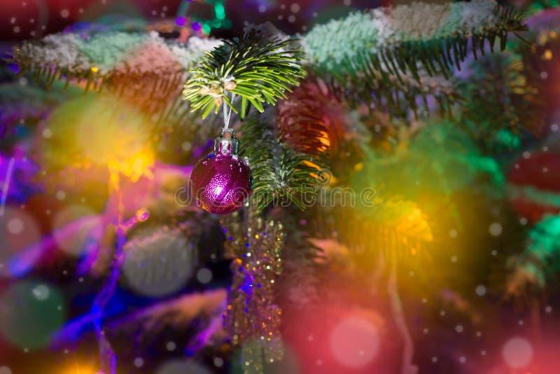 Árbol de navidad en la nieve adornada con los juguetes y las luces coloreadas imagenes de archivo