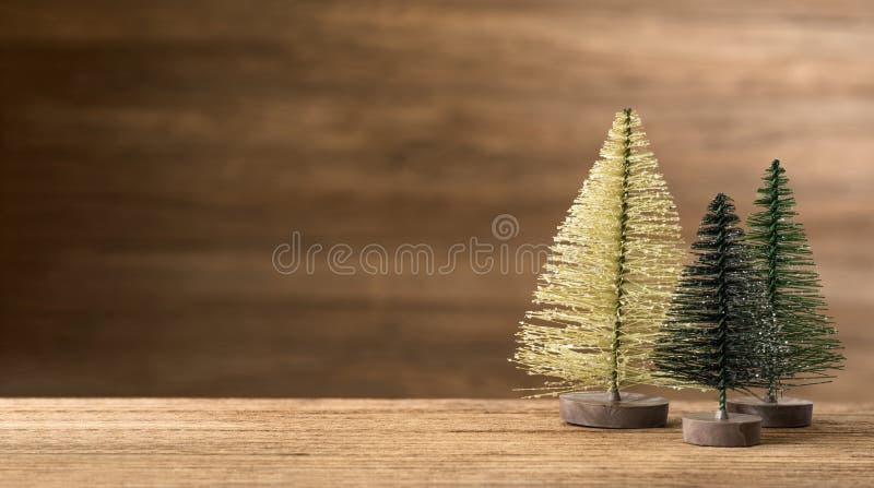 Árbol de navidad en la tabla de madera con la pared de madera para los felices chirstmas y backgrond de la tarjeta de felicitació fotografía de archivo