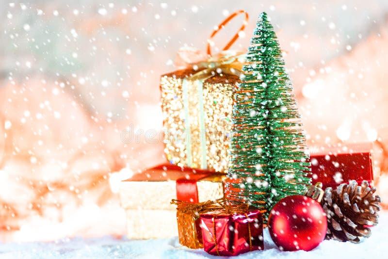 Árbol de navidad en nieve con el regalo y fondo festivo ligero de los fondos del bokeh, de la Navidad Nevado o del Año Nuevo imagen de archivo