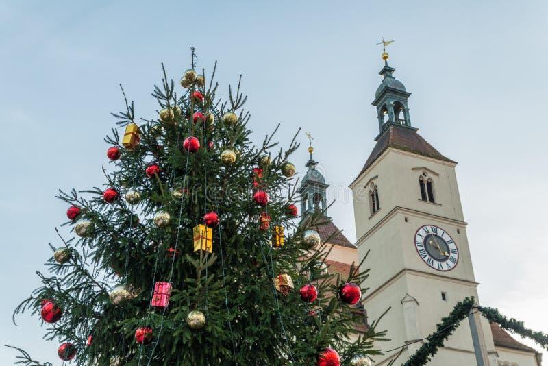 Árbol de navidad en un mercado de la Navidad en Regensburg con la vista a la nueva iglesia parroquial, Alemania imágenes de archivo libres de regalías