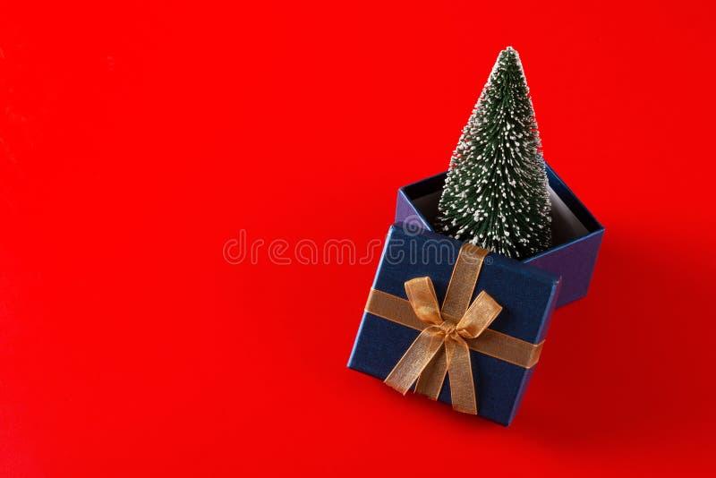 Árbol de navidad en una actual caja en rojo fotos de archivo libres de regalías