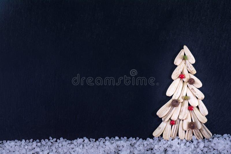 Árbol de navidad hecho con la semilla de girasol seca con pimienta colorida, en un fondo de la pizarra imagen de archivo libre de regalías