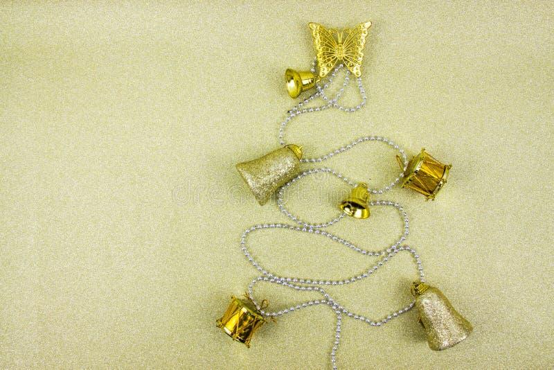 Árbol de navidad hecho de decoraciones de oro del invierno en fondo del oro con el espacio vacío de la copia para el texto creati foto de archivo libre de regalías