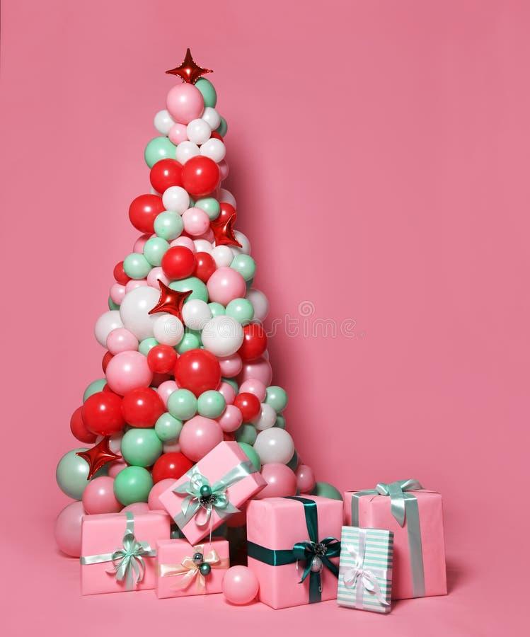 Árbol de navidad hecho de muchas cajas de los globos del color en colores pastel y de los regalos del rosa del color en colores p fotos de archivo