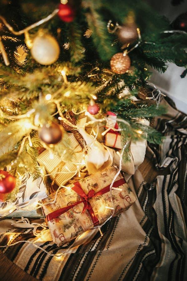 Árbol de navidad hermoso con los ornamentos, luces y prese de oro imagenes de archivo