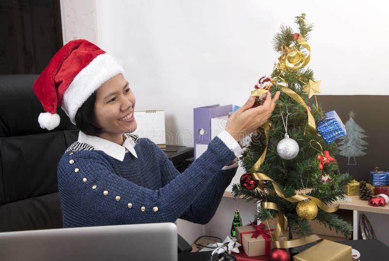 Árbol de navidad de la decoración de la mano de la mujer de negocios en el escritorio foto de archivo libre de regalías
