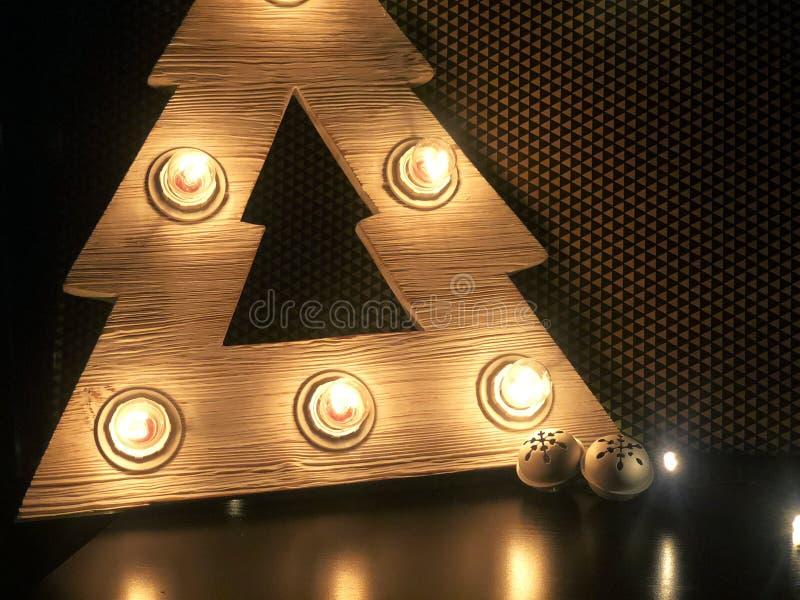Árbol de navidad de madera con las lámparas Juguetes de la Navidad en la tabla fotos de archivo