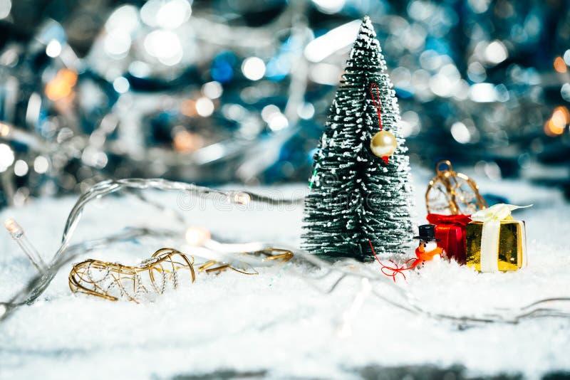 Árbol de navidad, muñeco de nieve y regalos miniatura en la nieve fotografía de archivo